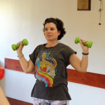 woman in exercise class lifting dumbell weights